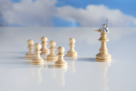 Chess piece king or queen with tin foil helmet on the head and a long lying nose stands in front of small game pieces, conspiracy theory concept, bright ground and very blurry sky with clouds, copy space, selected focus, narrow depth of field Stock Photo