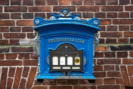 Historical blue post box on a brick wall in Lauenburg in northern Germany on the river Elbe, still in use and now a tourist attraction, selected focus, narrow depth of field