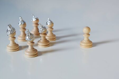 Group of pawn chess pieces with tinfoil hats against imagined heteronomy stand towards a piece without hat, conspiracy theory and manipulation concept in coronavirus time,  gray background, copy space, selected focus, narrow depth of field