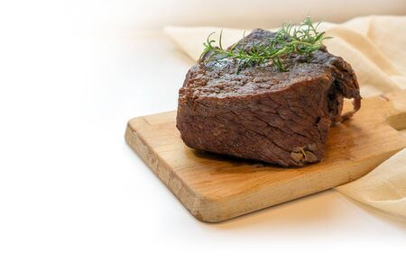 Piece of roast beef braised in red wine with thyme garnish on a cutting board, typical preparation for boeuf bourguignon, the light background is fading to white, copy space, selected focus, narrow depth of field