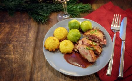 roasted duck with duchess potatoes, brussels sprout and sauce, served as a festive christmas dinner on a dark wooden table, copy space, selected focus, narrow depth of field
