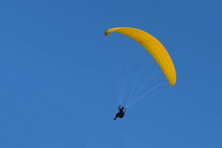 Paraglider pilot with a yellow glider is flying in the clear blue sky, recreational and competitive adventure sport, copy space