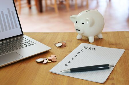 Calculating household costs, laptop, coins, a piggy bank and a list what to pay on a table in the living room, economy finance concept to save money, selected focus, narrow depth of field