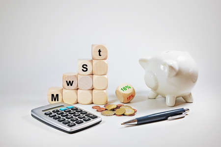 Calculator, piggy bank and dices with German text MwSt (value added tax), reduction from 19% to 16%, economic stimulus package in the coronavirus crisis to promote financial investments, gray background, copy space, selected focus