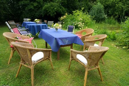 Set up for a casual summer party with tables, blue tablecloths and many different chairs in a rural garden, selected focus
