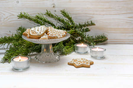 Gingerbread cookies for Christmas on a crystal glass bowl, burning candles and fir branches on a white painted wooden table, copy space, selected focus