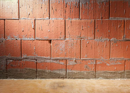 Wall of Porotherm style clay block bricks in a building under construction, background with copy space, lit laterally