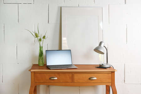 Small vintage table of reddish wood with laptop, desk lamp and a picture frame in front of a raw white wall, tiny home office place in the living room, copy space, selected focus, narrow depth of field