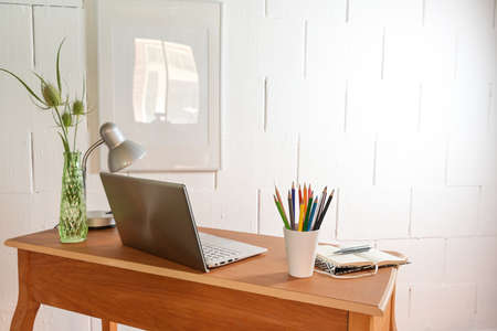 Small wooden home office desk from behind with laptop and tools against a rough white wall, copy space, selected focus, narrow depth of field
