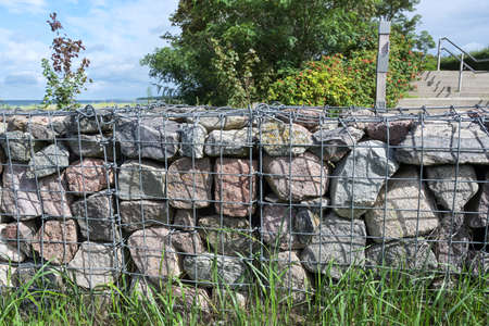 Gabions, stones in wire cages are a modern design option in gardens and landscapes as fortifications or boundary walls, selected focus