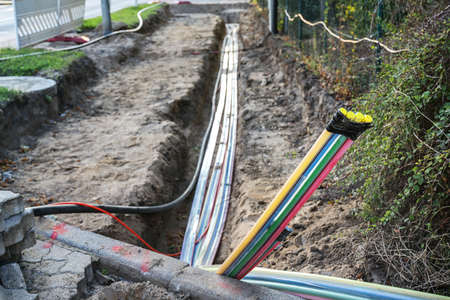 Construction site for installing fiber optic cables under the ground beside a street to bring fast internet to all residents, selected focus, narrow depth of field