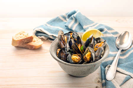 Bowl with mussels, lemon and herbs, a blue towel, spoon and bread on a light wooden table, copy space, selected focus, narrow depth of field