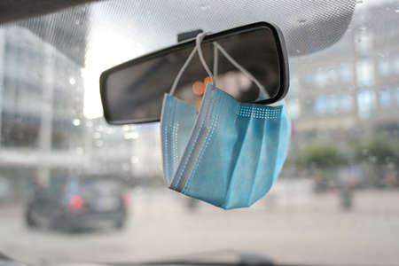 Surgical face mask as protection against covid-19 infection is hanging in a car on the rear view mirror during the coronavirus pandemic, copy space, selected focus, narrow depth of field