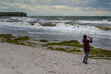 Woman takes photos of wild waves in storm and onshore wind at the beach of Boltenhagen at the Baltic Sea in Germany, copy space, selected focus, narrow depth of field 版權商用圖片