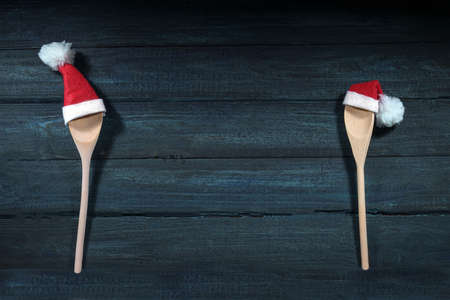 Two cooking spoons with red Santa Claus hats apart on both sides of a dark blue wooden background, copy space in the middle, Christmas invitation for a social distance dinner or greeting card, top view from above