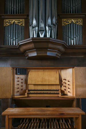 Pipe organ console with two keyboards or manuals, stop knobs, pedal board, and case facade in the St. Mary's Church of Gudow, Germany, selected focus
