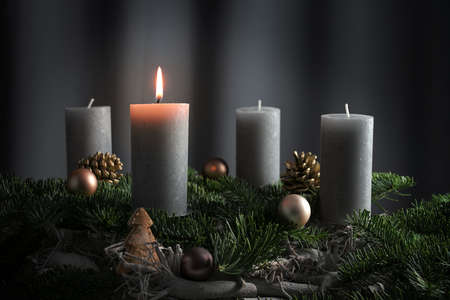 Four candles, one of them lit on an advent arrangement from fir branches and Christmas ornaments, holiday decoration against a dark gray background with copy space, selected focus, narrow depth of field