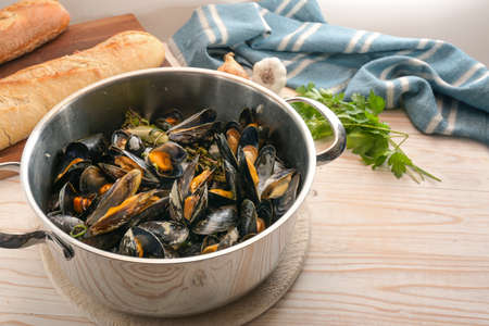 Freshly cooked mussels in a pot, bread, herbs and a blue towel on a wooden kitchen table, healthy seafood meal, copy space, selected focus, narrow depth of field