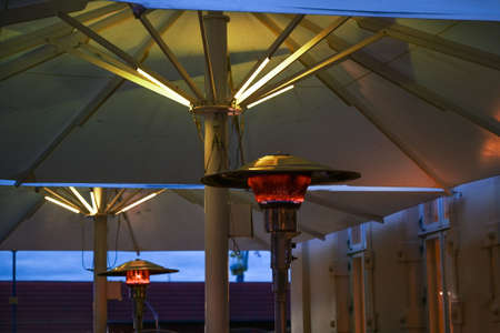 Gas burning patio heater on a restaurant terrace with bad environmental effects, allows dining outside, which reduces the risk of infection during coronavirus pandemic, selected focus, narrow depth of field