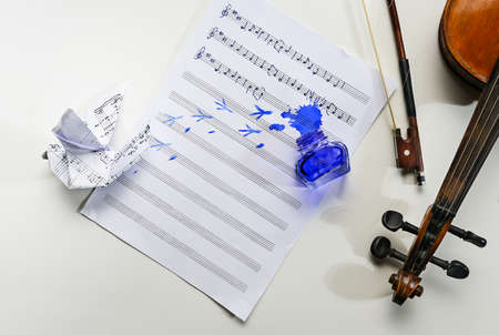 Sheet of music with handwritten folk song All the birds are already here, overturned ink jar, bird footprints and an origami dove, violin and bow on the side, concept for composers misfortune, copy space, selected focus, view from above Stock Photo