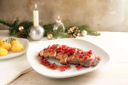 Festive holiday meal from roasted duck with pomegranate seeds and duchess potatoes on a white plate, rustic background with candles and Christmas decoration, copy space, selected soft focus, narrow depth of field