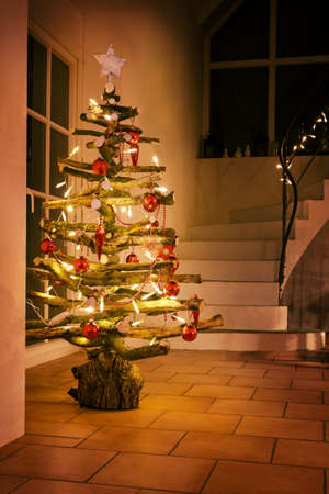 Rustic Christmas tree made of raw wood branches decorated with glowing fairy lights and red balls in a stairwell at night, selected focus, narrow depth of field