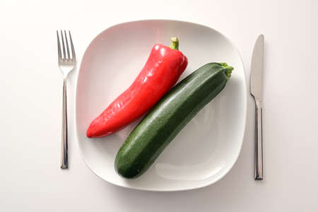 Raw red pointed pepper and zucchini on a white plate and cutlery on a bright background, healthy diet with mediterranean vegetables to lose weight in the new year, copy space, high angle view from above