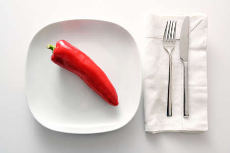Raw red pointed sweet pepper on a white plate, cutlery and napkin beside on a bright background, healthy eating with vegetables or diet to lose weight as a good resolution in the New Year, copy space, high angle view from above