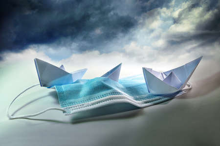Three paper boats struggle against sinking on a surgical face mask under a stormy sky
