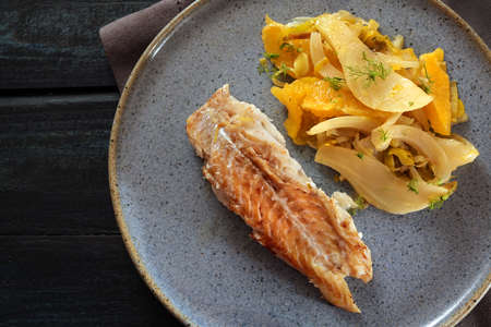 Cod fish with fennel vegetable and orange slices on a blue plate and a dark table, high angle view from above, selected focus