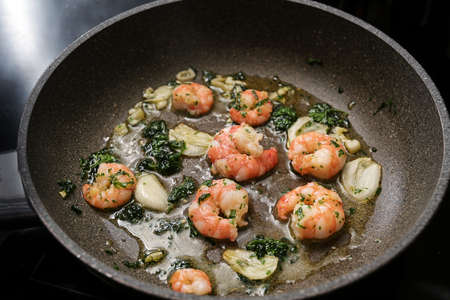 Shrimps or black tiger prawns are sauteed with olive oil, garlic and parsley in a frying pan for a delicious seafood snack, selected focus, narrow depth of field