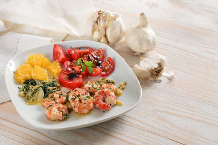 Appetizer plate with fried shrimps, sauteed herb garlic, tomato salad and marinated citrus fruit on bright wooden table, copy space, selected focus, narrow depth of field