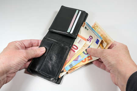 Hands taking various euro banknotes out of a black leather wallet, money and finance concept, light gray background, selected focus, narrow depth of field