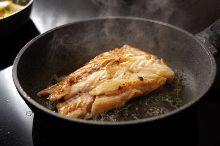 Cod fish fillet sautéed with thyme in a steaming frying pan on the black stove, copy space, selected focus, narrow depth of field