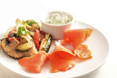 Smoked salmon with vegetables and dip on a white plate, healthy snack with low calories for a slimming diet, selected focus, narrow depth of field Stock Photo