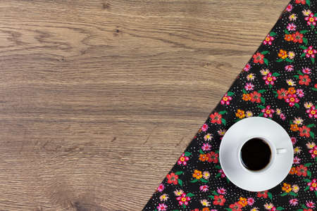 Coffee on pattern flower cloth napkin on empty wooden background. Top view with space for your text.