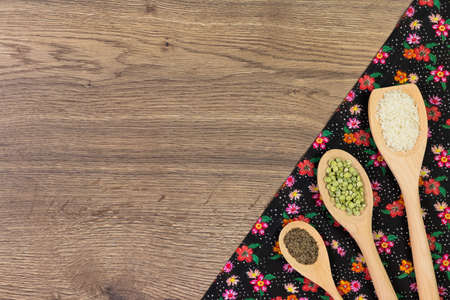 Set of spoons with rice, peas e black pepper. Pattern flower cloth napkin on empty wooden background. Top view with space for your text.