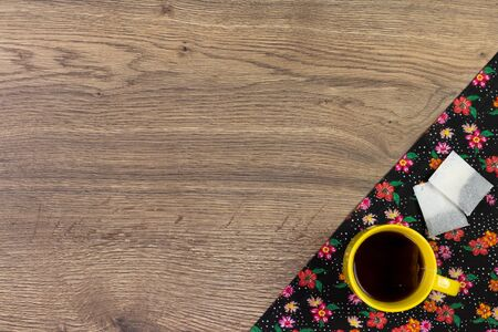 Tea mug on pattern flower cloth napkin on empty wooden background. Top view with space for your text.