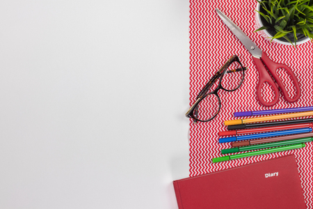 Fashion designer workplace. Modern white office desk table with a notebook diary, eyeglasses and colorful pens. Top view with copy space, flat lay.
