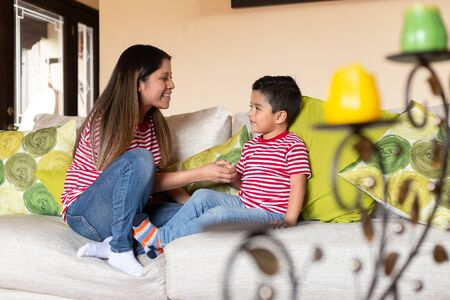 Hispanic mom with her 4 year old son playing and talking