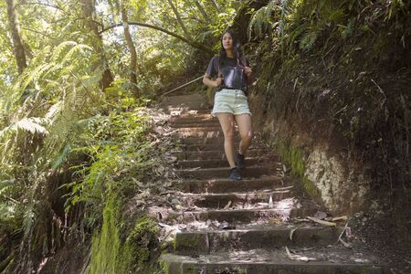 Caucasian woman in a tropical forest in summer walking and smiling in the middle of nature