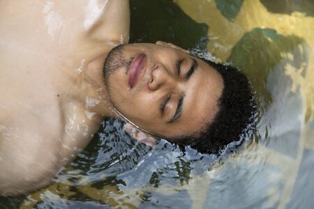 Portrait of Hispanic man floating in a natural pool with eyes closed- Man relaxing in hot springs in Guatemala