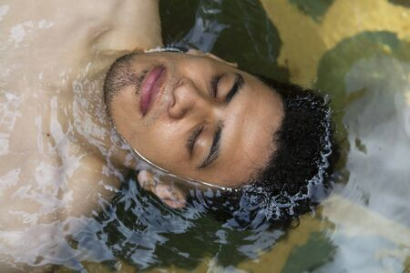Portrait of latin man floating in a natural pool with eyes closed- man relaxing in hot springs in Guatemala- close up