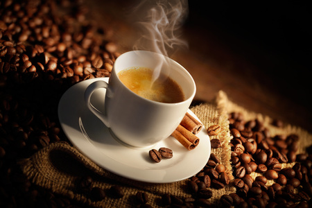 Cup of espresso with coffee beans and cinnamon