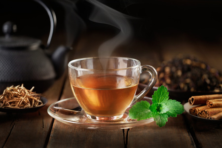cup of hot tea with teapot, mint and spices