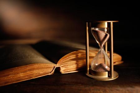 stara klepsydra i starożytna księga z otwartymi stronami
