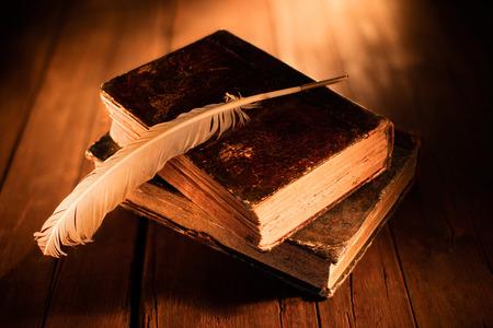 Alte Bücher mit Federkiel auf Holztisch