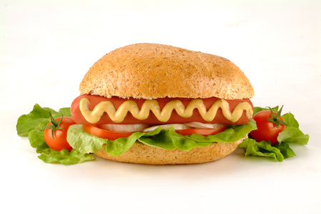 hot dog with wurstel, cheese, tomatoes, salad and mustard Standard-Bild - 99389323
