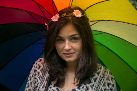 Girl playing with a rainbow umbrella in the garden.