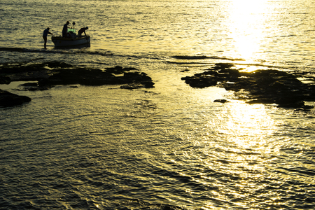 returned: fishermen at sunset, returned to the harbor, golden hour. Livorno, Italy. Stock Photo